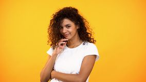 Pretty young woman dreaming orange background, making wish, flirting, shy female stock image