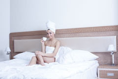 Pretty young woman drinking coffee in bed Stock Photos