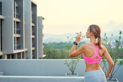 Pretty young woman drinking. Healthy lifestyle. Pretty young woman in sports wear with smartwatch tracker holding bottle of water outdoors Royalty Free Stock Photography