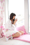 Pretty young woman drinking her morning coffee Stock Photos