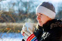 Pretty young woman drinking hot tea on a cold winter day. Beautiful woman drinking tea on the street in winter Stock Image