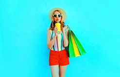 Pretty young woman drinking juice holding shopping bags in colorful t-shirt, summer straw hat, sunglasses, red shorts on blue stock image