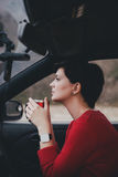 Pretty young woman drinking tea in a car with rain outside Royalty Free Stock Image