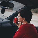 Pretty young woman drinking tea in a car with rain outside Stock Photo