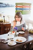 Pretty  young woman drinking tea or coffee in a cafe Royalty Free Stock Photos