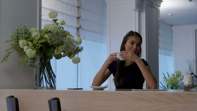 Pretty young woman drinking tea and flirting in a coffee shop stock footage