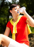 Pretty young woman drinking water in the park Royalty Free Stock Photos
