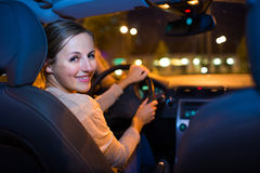 Pretty young woman driving  car at night Royalty Free Stock Image