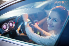 Pretty young woman driving her brand new car royalty free stock photo