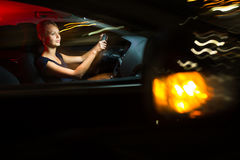 Pretty, young woman driving her modern  car at night, in a city Stock Photography