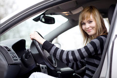 Pretty young woman driving her new car Stock Photography