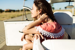 Pretty young woman driving on road trip on beautiful summer day. Royalty Free Stock Images