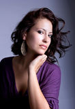 Pretty young woman with ear-ring, studio shot Royalty Free Stock Photo