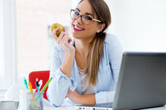 Pretty Young Woman Eating An Apple In Her Office. Stock Photos