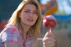 Pretty young woman eating and biting red caramel apple in the park in the sunny day. Alone smile happy stock photo