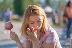Pretty young woman eating and biting red caramel apple in the park in the sunny day. Alone smile happy stock image