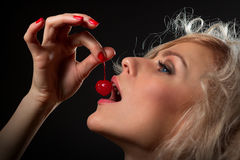 Young woman eating cherry. Pretty young woman eating the coctail cherry Stock Photos