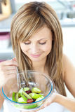 Pretty young woman eating a fruit salad at home Royalty Free Stock Photography