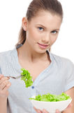 Pretty young woman eating lettuce salad. Isolated. Pretty young woman eating lettuce. Salad. Isolated on the white background royalty free stock photo