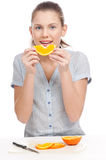 Pretty young woman eating orange. Isolated Royalty Free Stock Image