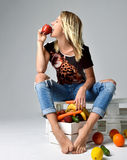 Pretty young woman eating red apple near box with fresh organic Royalty Free Stock Photography