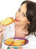 Pretty Young Woman Eating A Slice of Garlic Bread Stock Images