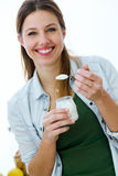 Pretty young woman eating yogurt in the kitchen. Stock Images