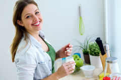 Pretty young woman eating yogurt in the kitchen. Stock Photos
