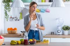 Pretty Young Woman Eating Yogurt While Standing In The Kitchen At Home Royalty Free Stock Photos
