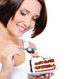 Pretty young woman eats a sweet cake Stock Photography