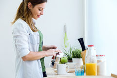Pretty young woman enjoying breakfast in the kitchen. Royalty Free Stock Photography
