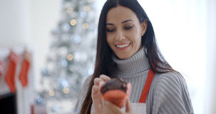 Pretty young woman enjoying her Christmas baking Stock Photo