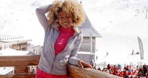 Pretty young woman enjoying her winter vacation. At a mountain ski resort posing on the balcony of a wooden chalet overlooking the village with crowds of stock video footage