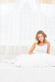 Pretty young woman enjoying morning time at her house lying in b Stock Photos