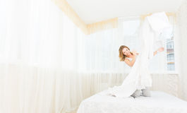 Pretty young woman enjoying morning time at her house lying in b Royalty Free Stock Image