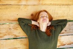 Pretty young woman enjoying a quiet stretch. With closed arms and hands behind her neck over a rustic wood background with copy space Stock Image