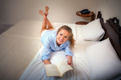 Pretty Young Woman Enjoying Reading on Bed Royalty Free Stock Images