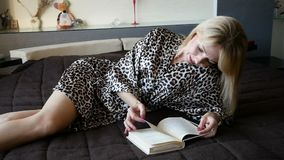 Pretty young woman enjoying reading a book at home lying on bed smiling in pleasure in dressing gown. Pretty young woman enjoying reading a book at home lying on stock video footage