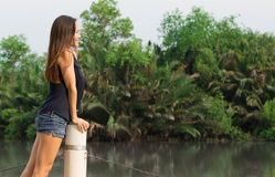 Pretty young woman enjoying the view at the pier on a warm afternoon. Young caucasian girl with slender build. Warm tropical background Royalty Free Stock Image