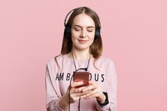 Pretty young woman enjoys nice music in headphones, watches funny videos, types messages on cell phone, dressed casually, isolated. Over pink background. People Royalty Free Stock Photos