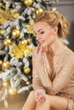 Pretty young woman in evening dress sits, smiles and looks side near Christmas tree. Young woman in evening dress sits, smiles and looks side near Christmas tree Royalty Free Stock Photos