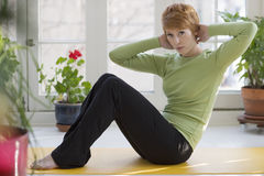 Pretty young woman exercising. Young woman doing sit-ups on exercise mat at home Royalty Free Stock Images