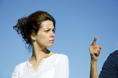 Pretty young woman facing accusation. Pretty young woman with angry facial expression looking back at an in accusation pointed arm. Clear blue sky and copy space Royalty Free Stock Images