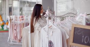 Pretty young woman in a fashion boutique stock video