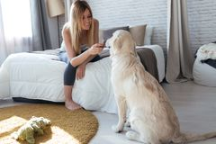Pretty Young Woman Feeding Her Dog While Having Fun At Home Royalty Free Stock Photo