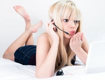 Blond woman in video conference with a headset lying on a bed