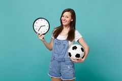 Pretty young woman football fan cheer up, support favorite team with soccer ball, round clock isolated on blue turquoise. Background in studio. People emotions stock image