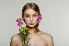 Pretty young woman with fresh spring look, wonderful hair, nice makeup, flowers near her face and in hair stock photography