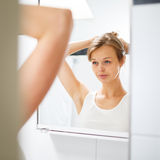 Pretty, young woman  in front of her bathroom mirror Stock Images