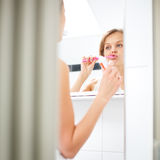 Pretty, young woman in front of the mirror. Morning stretch - Pretty, young woman in front of the mirror in the bathroom on an early morning Royalty Free Stock Photo